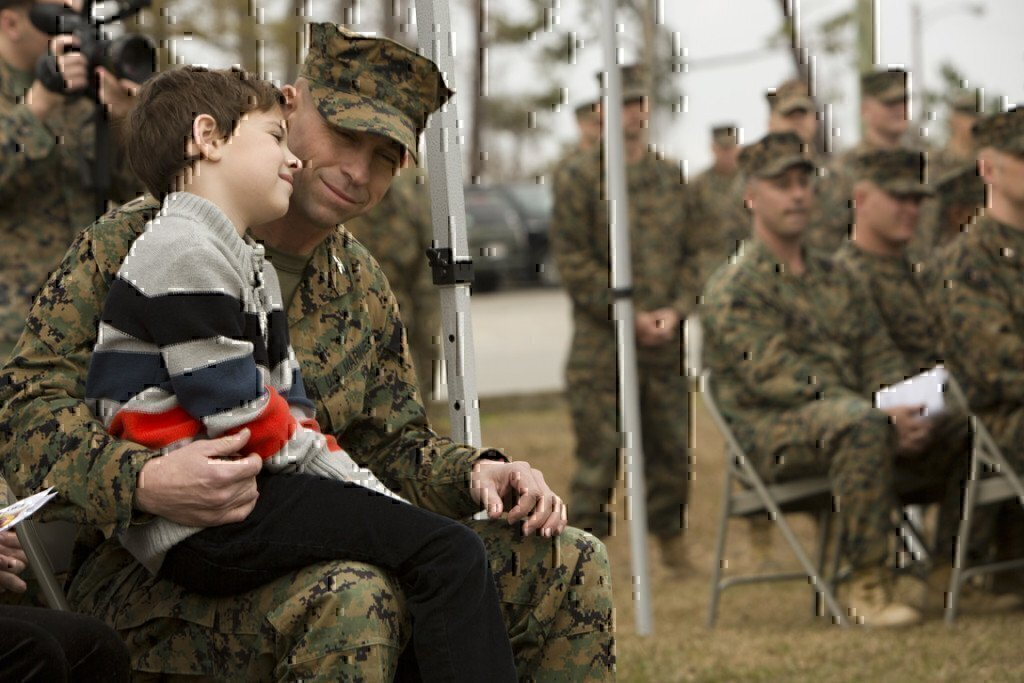 a marine father with his son on his lap