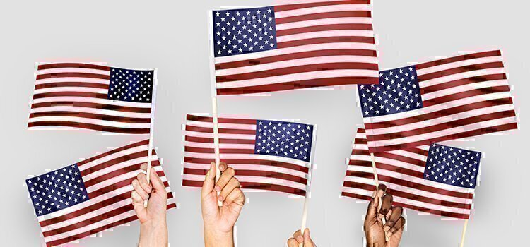 a group of hands holding small american flags
