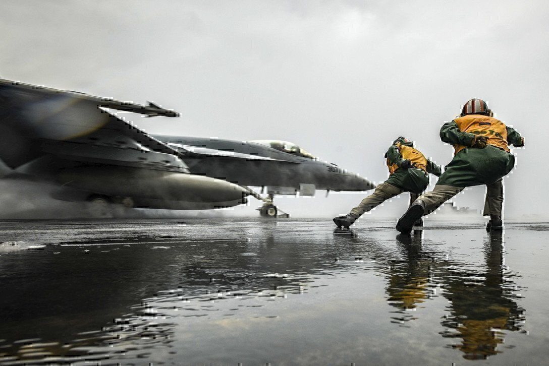 photo shows two sailors and a fighter jet taking off