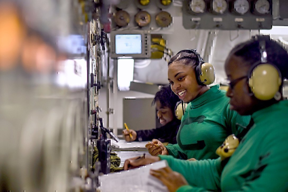 photo shows three female Navy members wearing headsets