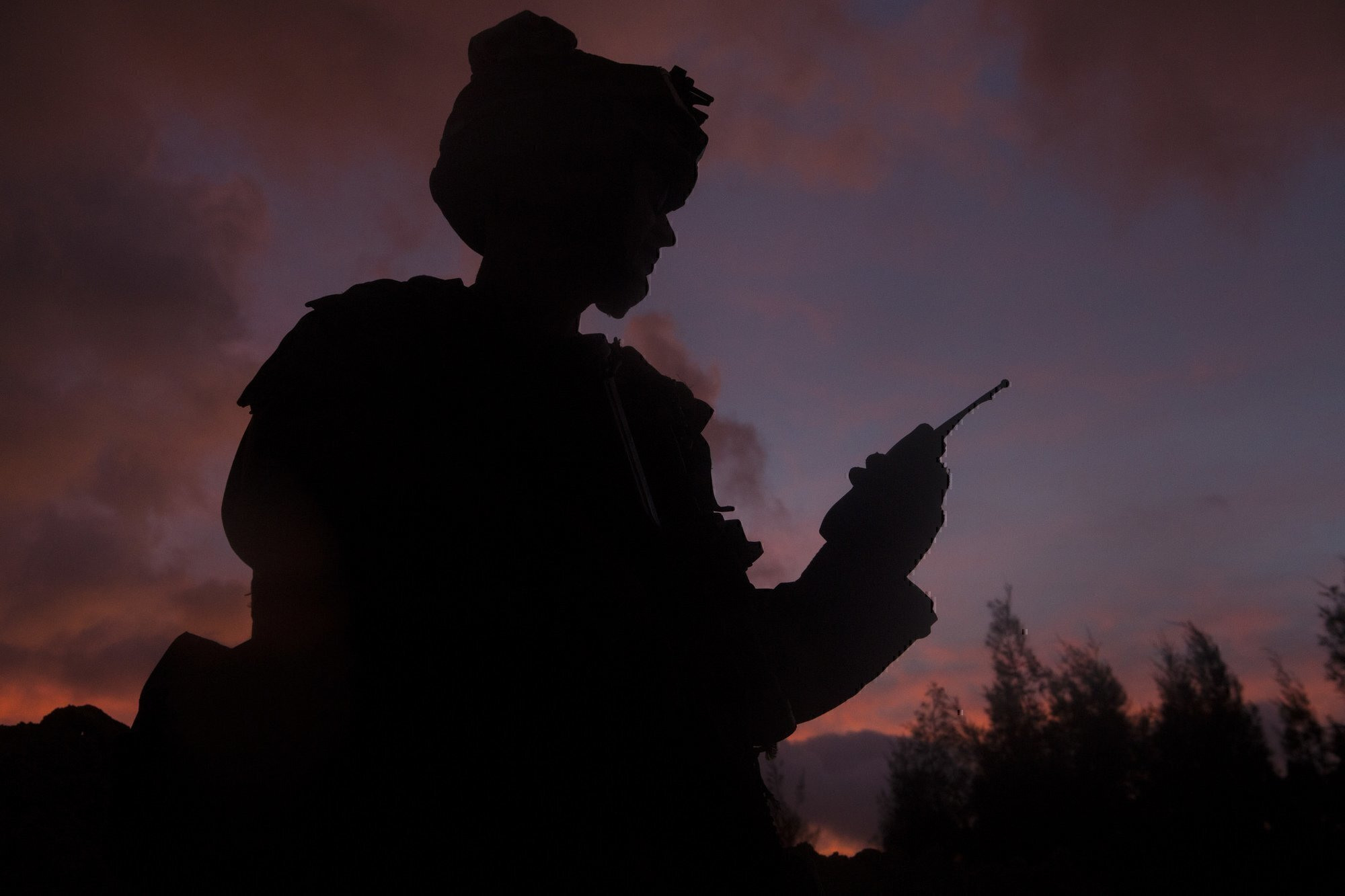 a soldier speaks into a radio, a common practice in IT Jobs