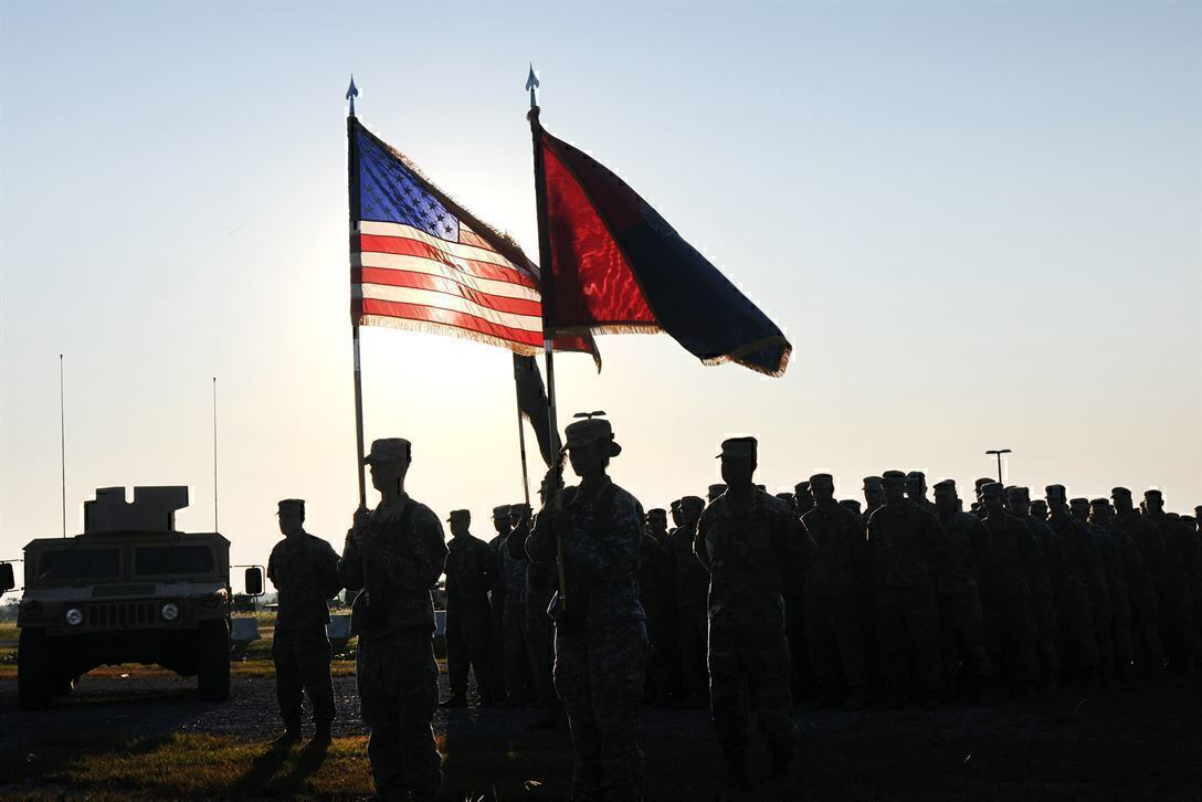 soldiers stand in a formation with two flags