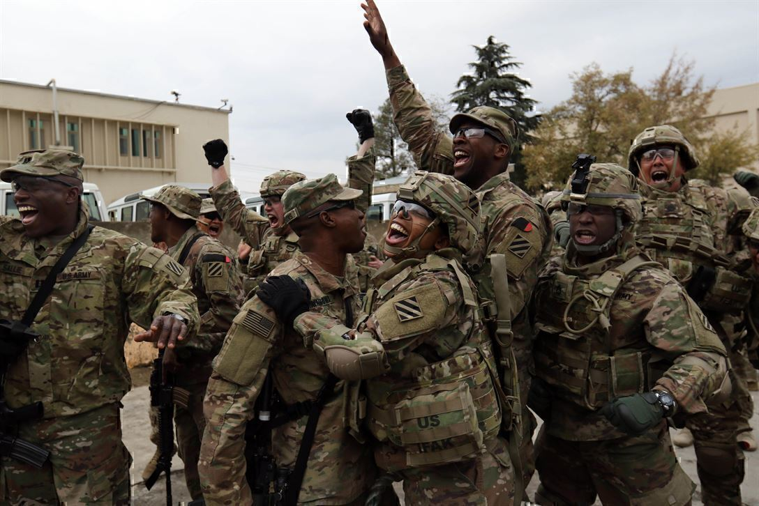 Soldiers gather in a group, cheering
