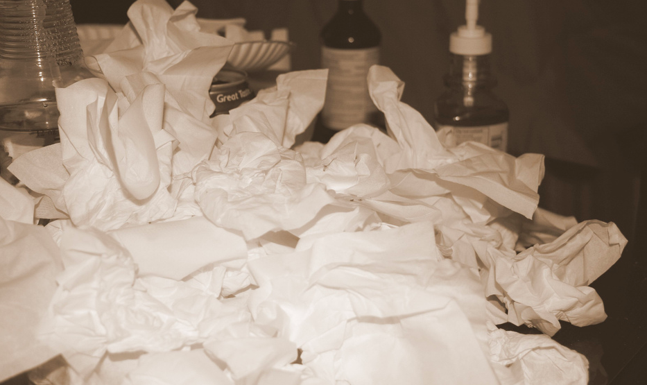 pile of tissues sitting next to a bed