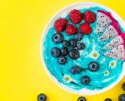 a bowl containing yogurt, blueberries and raspberries