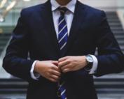 man wearing suit buttoning his jacket