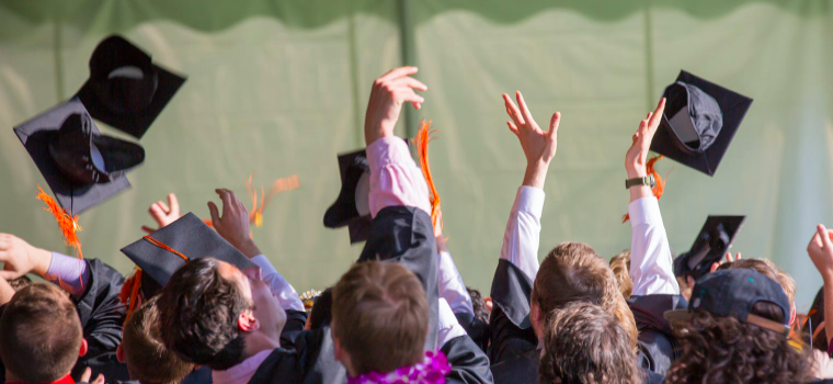 A group of students tosses their graduation caps in the air