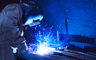 a welder welds a piece of metal