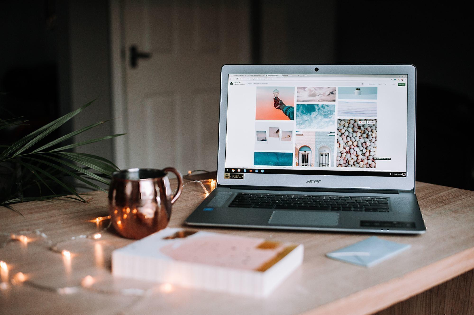 a computer sits on a table with a mug