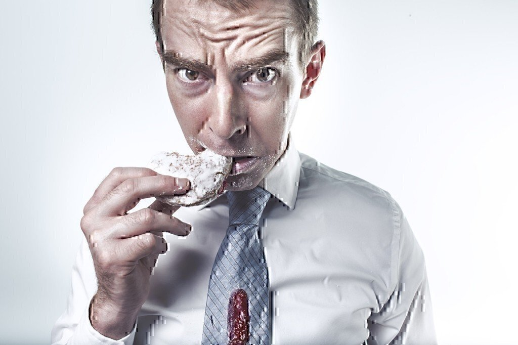 man eating donut spilled on shirt