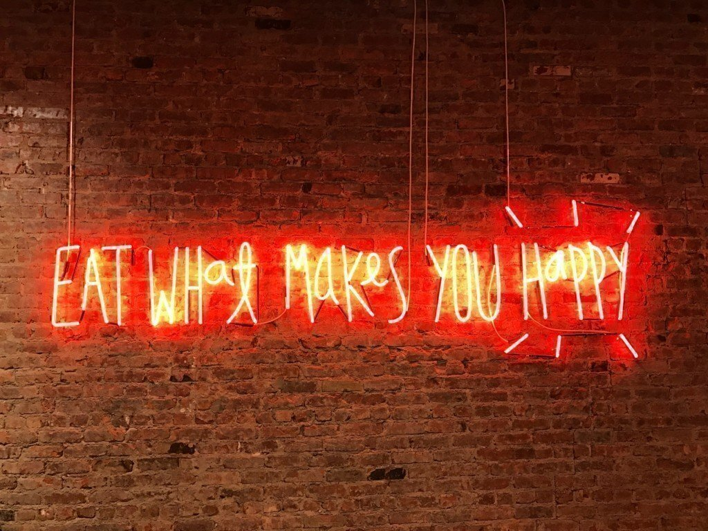 A red neon sign against a brick wall that says eat what makes you happy
