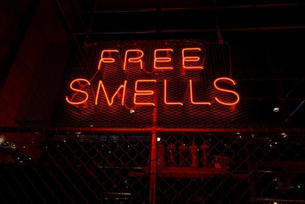 red neon sign that says free smells