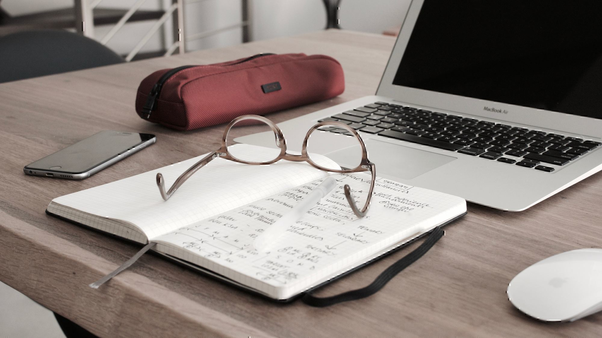 a pair of glasses sits on a notepad in front of a computer