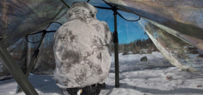 man-in-military-camo-sitting-in-snow-under-tent