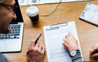 two people point to a paper contract on a table