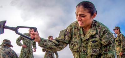 A Navy recruit digs a hole on the beach