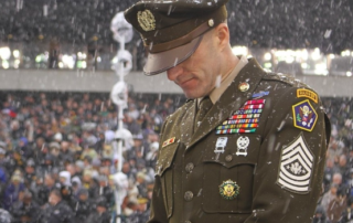 An army soldier stands in his dress green uniform