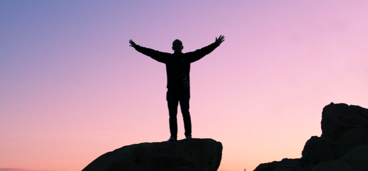 a man stands on a mountain top in the twilight