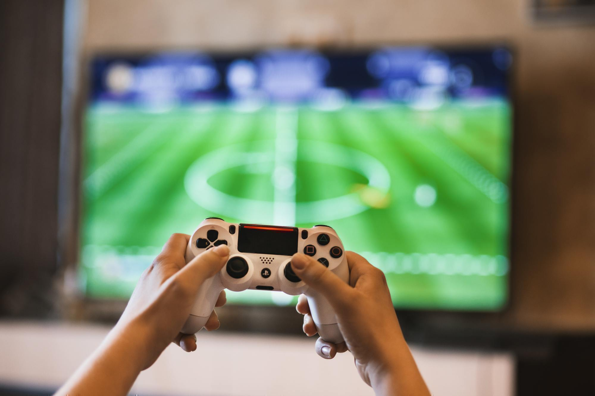 a person holds a video game controller in front of a television