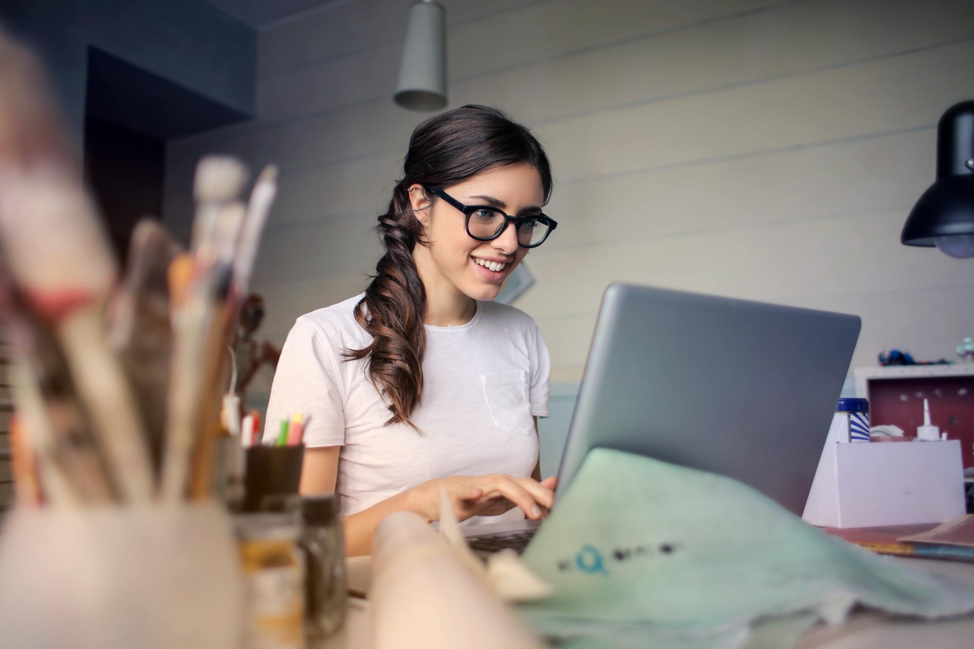 a girl wearing glasses smiles as she works on a computer
