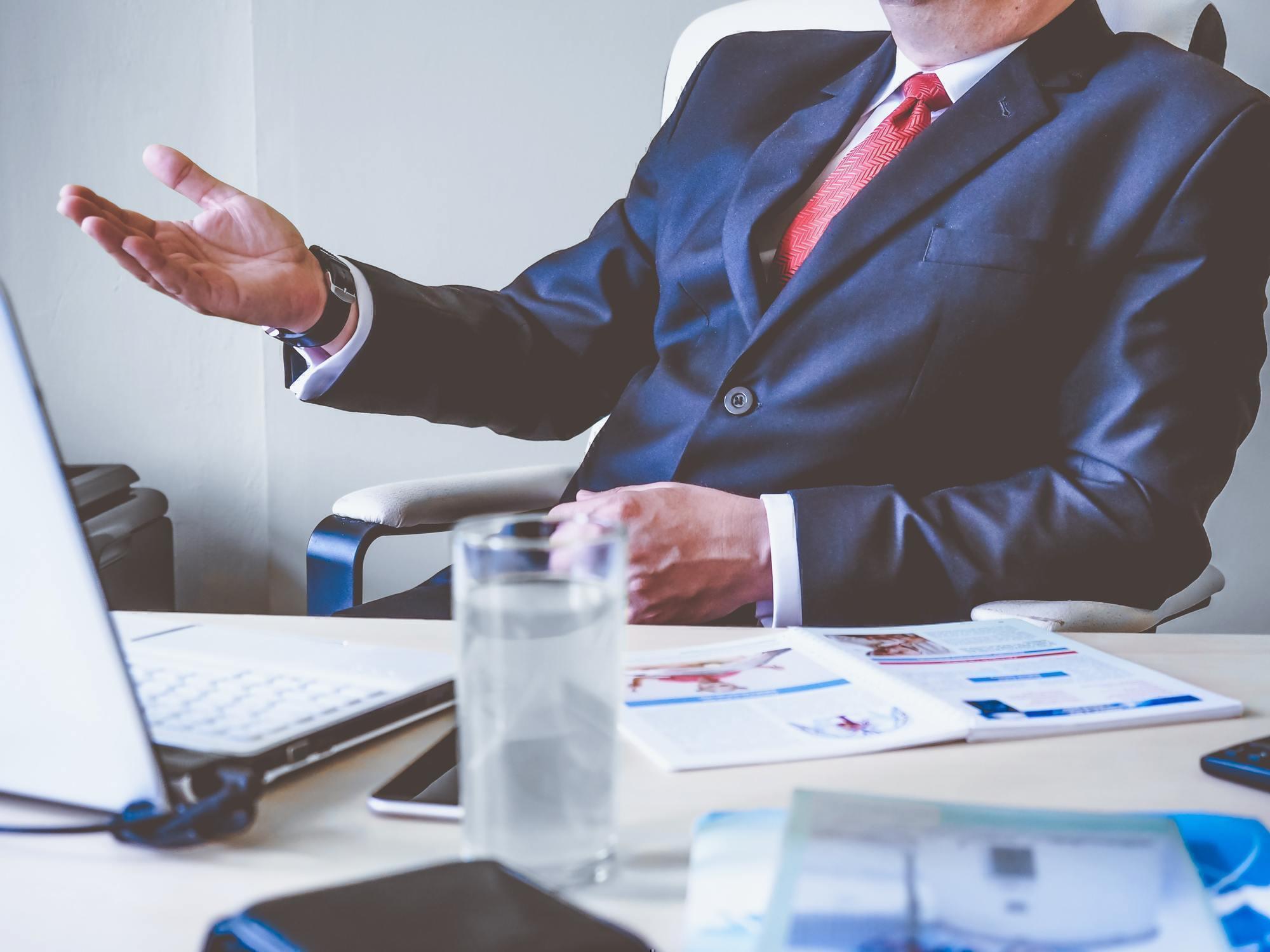 a man wearing a suit talks across a desk