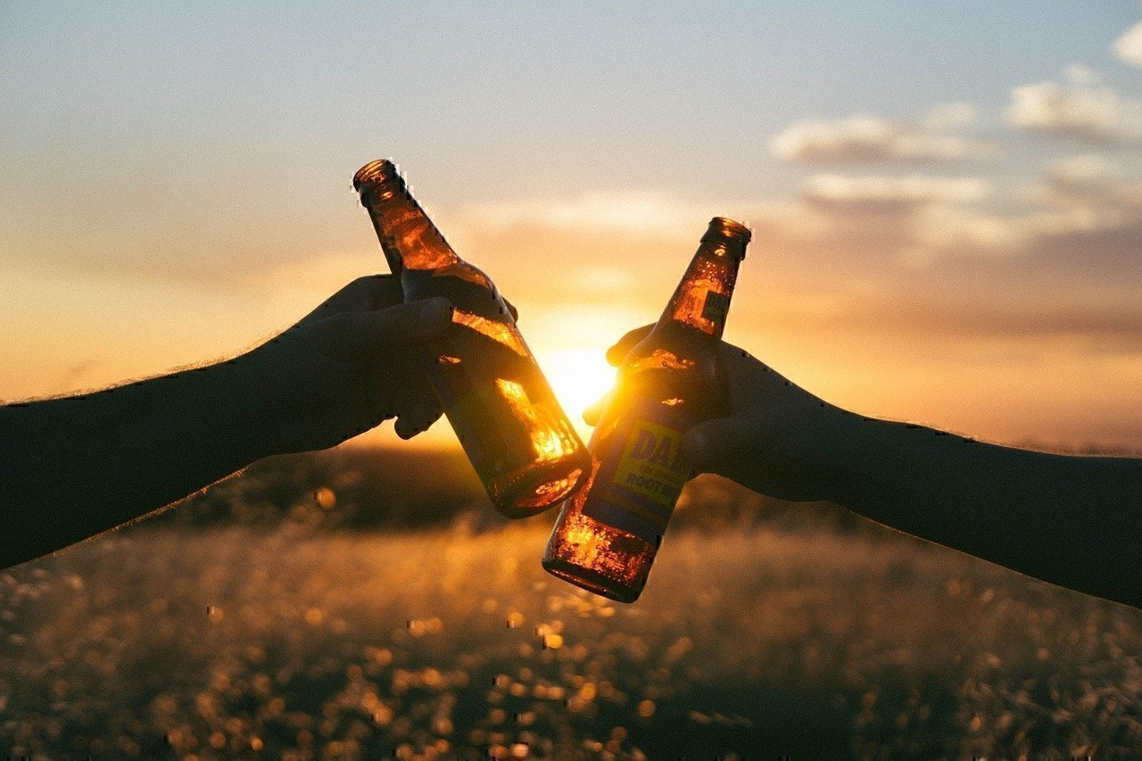 two people tap bottles of beer together in the sunset