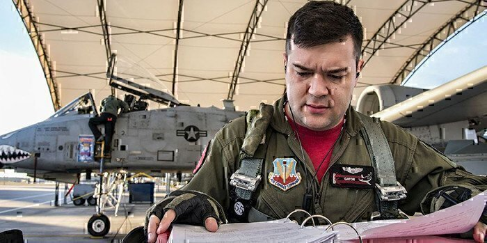 a pilot looking through a guide with his jet in the background