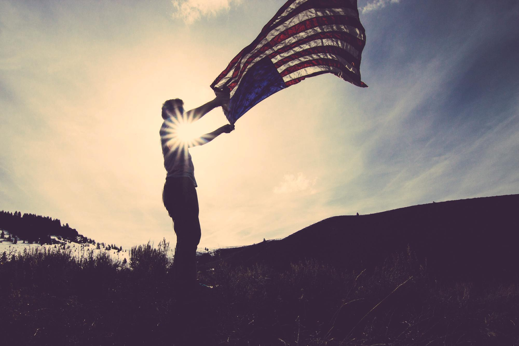 a man holding up an american flag in the sunlight