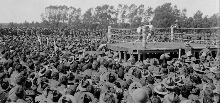 a group of soldiers watching a boxing match during world war one