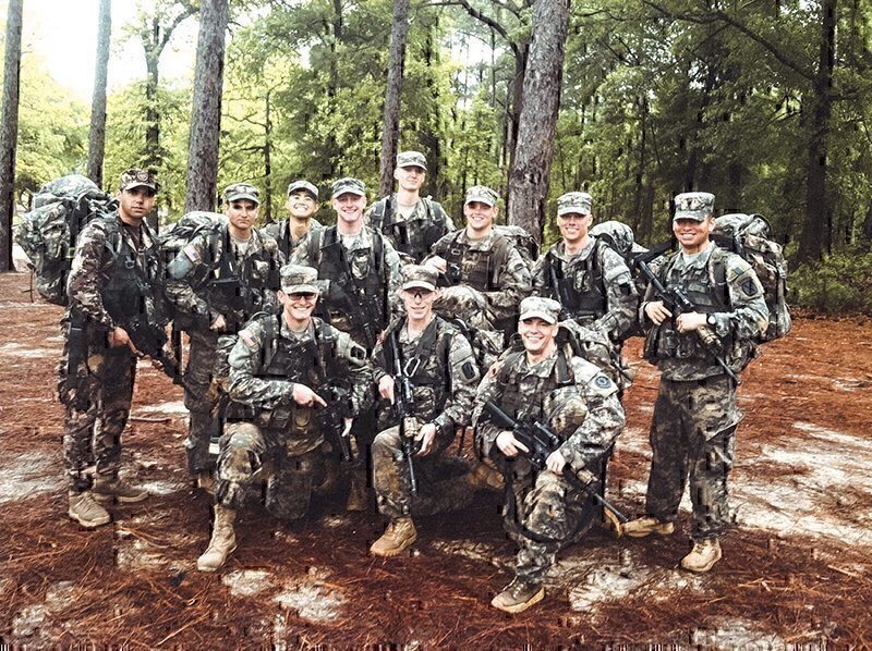 a group of soldiers smiling for a picture in the field