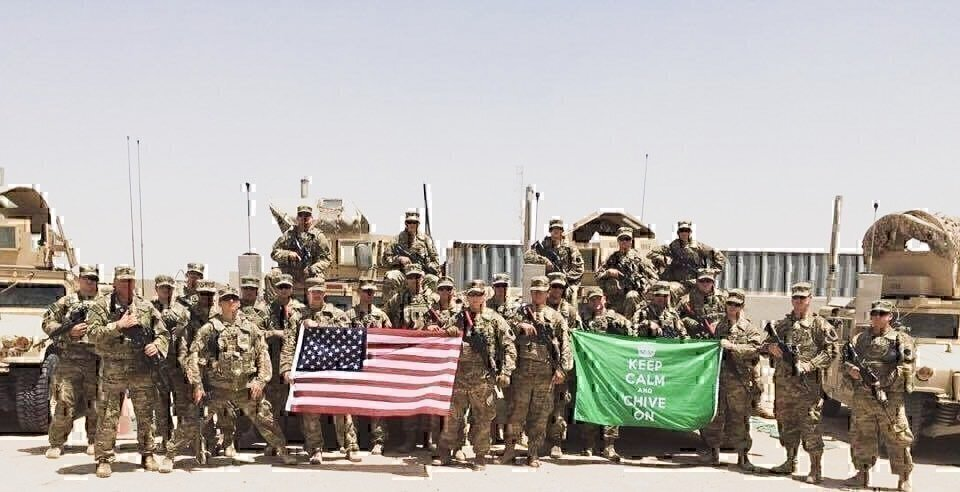 soldiers on deployment holding the american flag in front of military vehicles