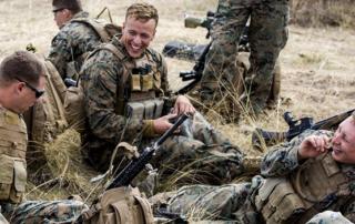 three soldiers in the field talking