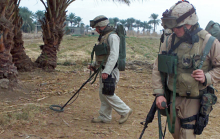 two soldiers scanning for explosives on a dirt trail