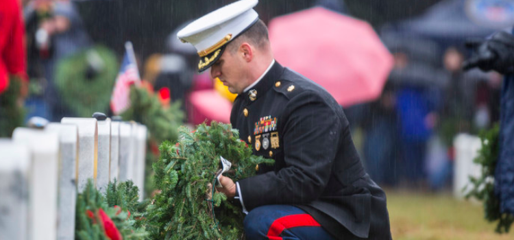 A Marine places a wreath on a tombstone