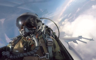 a fighter pilot sits in the cockpit during a flight