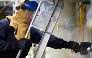 a u.s. sailor performs maintenance on a ship