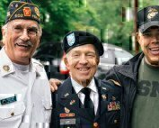 three veterans standing together smiling for a picture