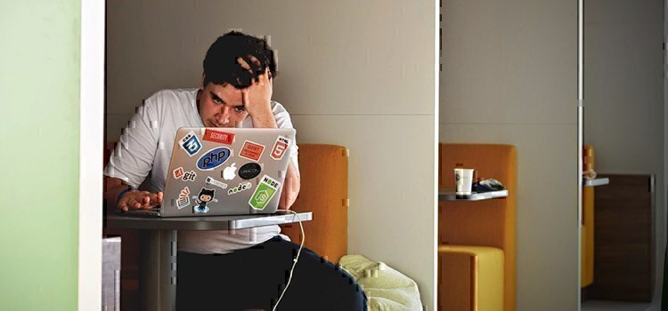 a man looking frustrated at his laptop