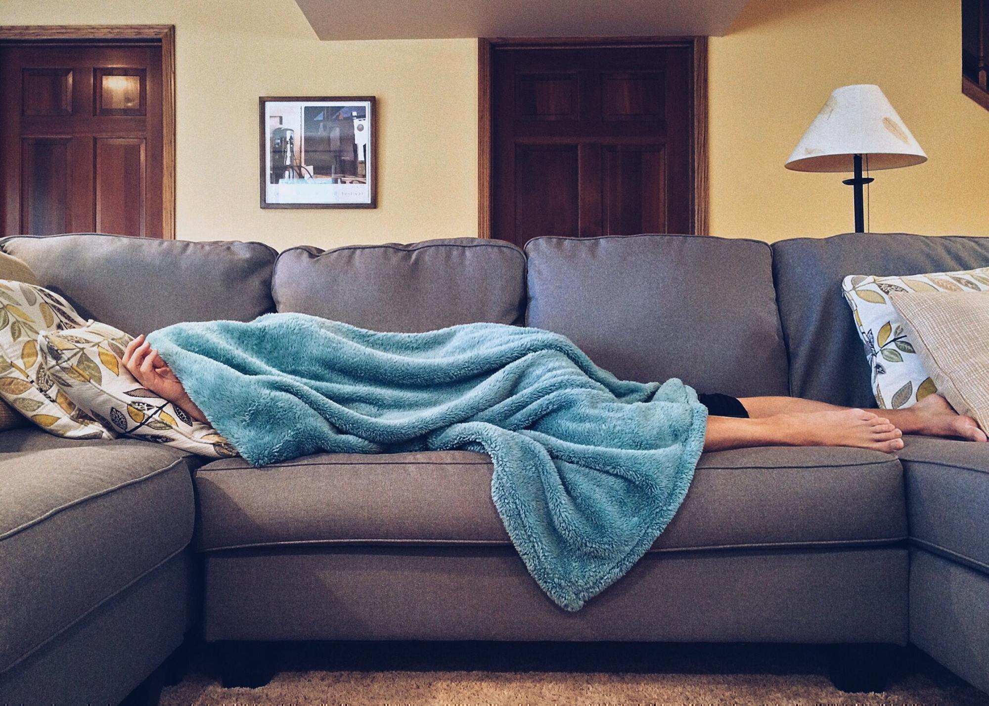 a sick person lays on a couch with a blanket over their head