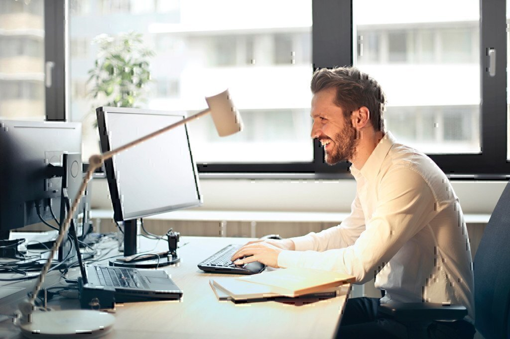 man smiling while working on a computer