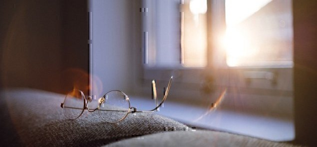 a pair of glasses on a desk with sunlight in the background