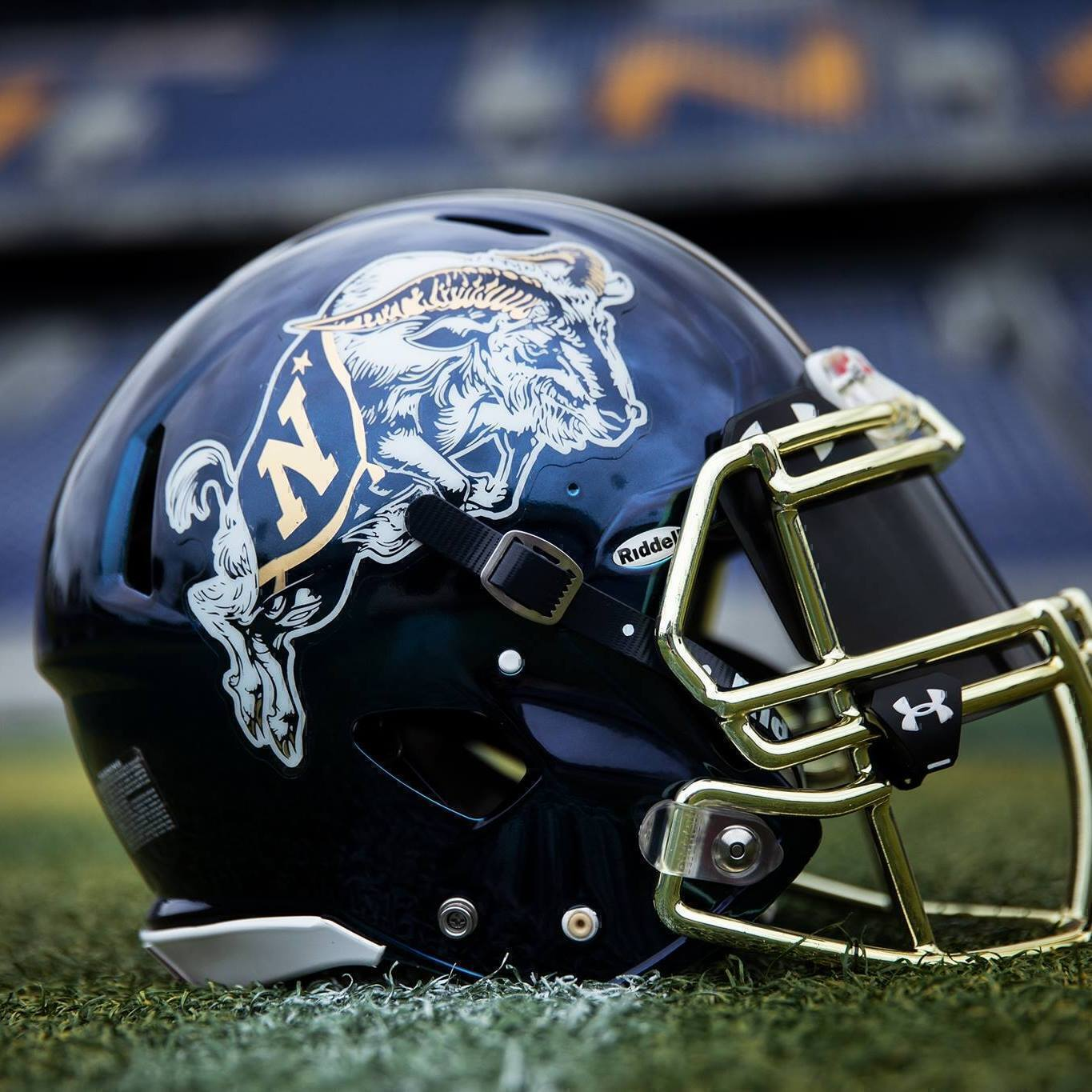 navy football helmet on the field close up