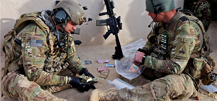 two soldiers eating an MRE on the ground