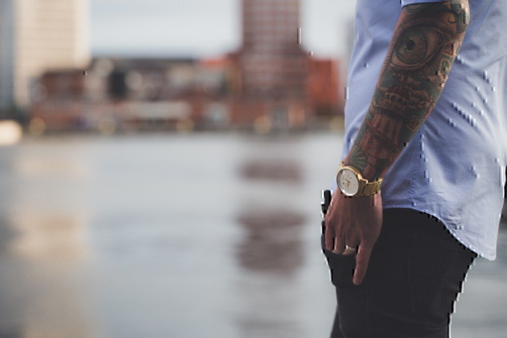 a man with an arm tattoo and a watch on