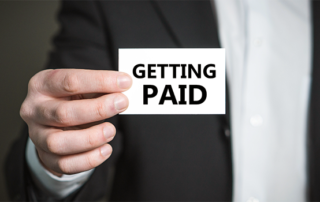 a picture of a man holding a card that says getting paid on it