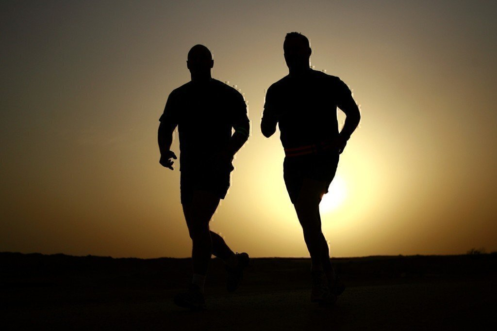 a picture of two guys running in the sunrise