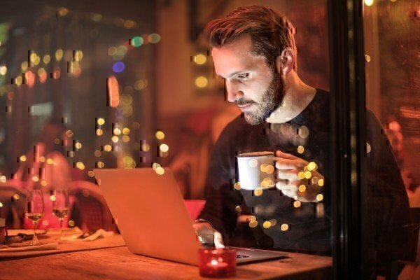 a man drinking coffee on a laptop
