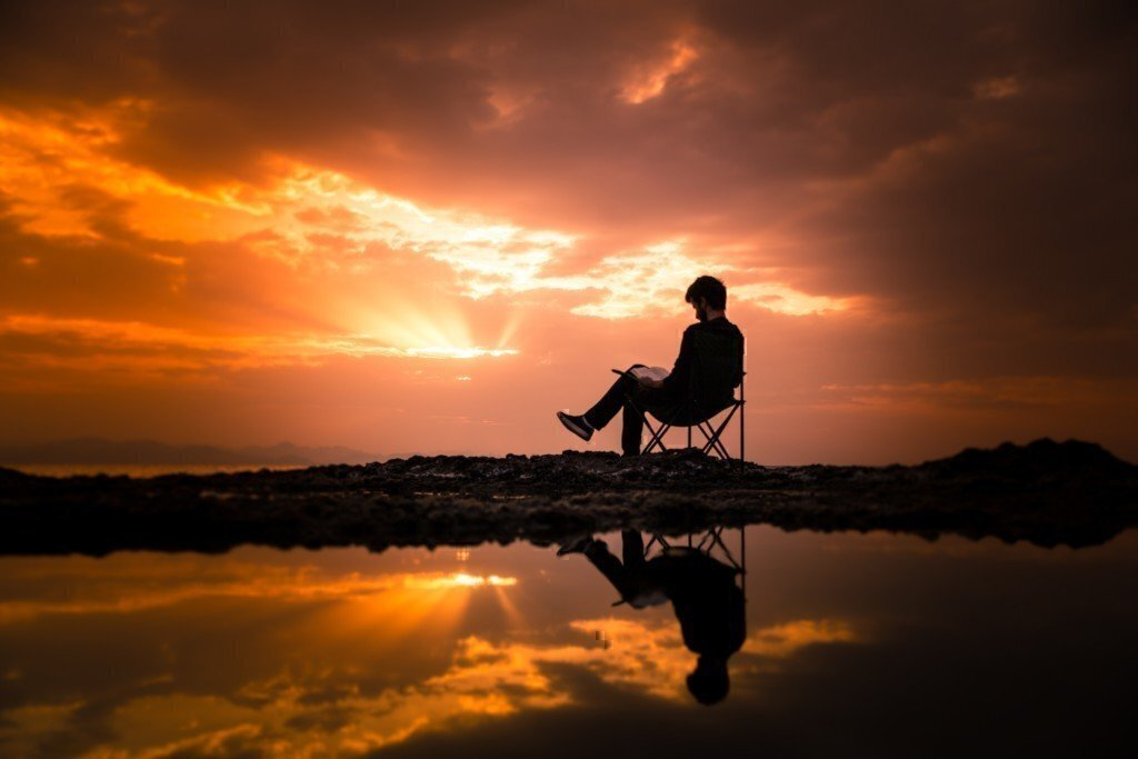 a person reading on a chair during sunset