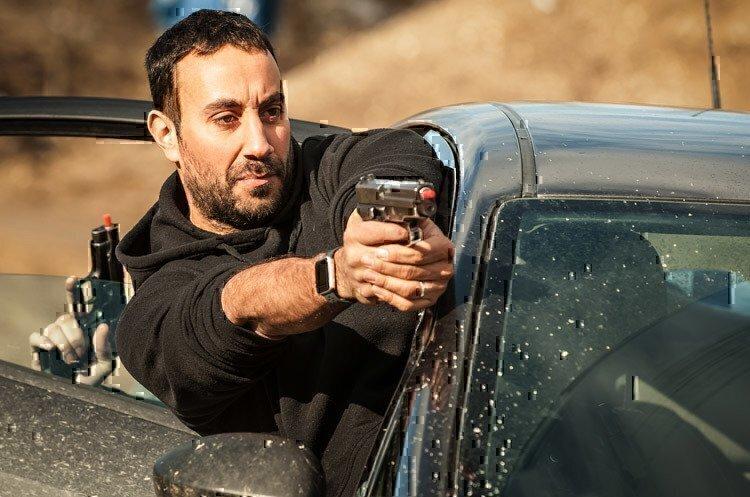 man-shooting-gun-from-car