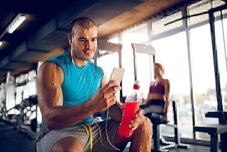 man-in-gym-looking-at-phone
